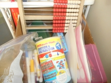 "cardboard box full of ""stuff"" crayons, markers, abacus, manipulatives, stickers"